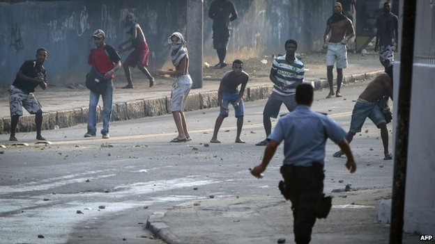 Men throw stones at police that entered an abandoned building occupied by squatters to evict them in Rio de Janeiro, April 11, 2014