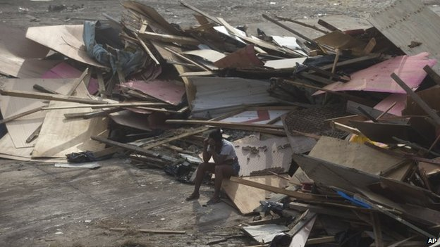 A woman sits on debris from makeshifts homes after an eviction in Rio de Janeiro, April 11, 2014.