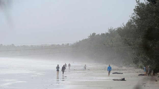 Onlookers walk along a beach to watch large waves created by strong winds on 12 April 2014 in Port Douglas, Australia
