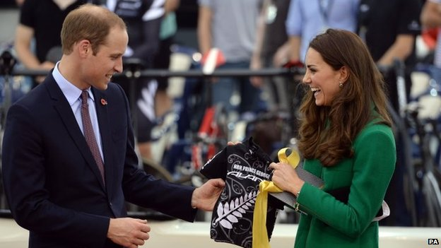 The Duke and Duchess of Cambridge holding a cycling jersey with Prince George's name on