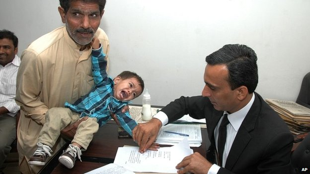 Muhammad Musa Khan cries as he provides fingerprints at a legal office in Lahore - 3 April 2014