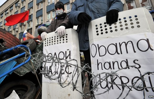 "Po-Russian activists hold shields signed ""Obama hands off Ukraine ""and ""Down with US and EU"" as they guard a barricade outside the secret service building in the eastern Ukrainian city of Luhansk on April 12,"