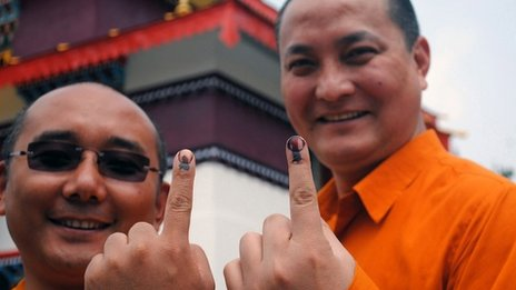 Buddhist monks display ink-stained fingers marked after voting in Sikkim state, India, 12 April