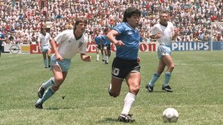 Diego Maradona powers through the England defence to score for Argentina