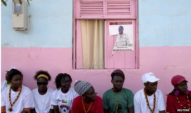 Youth supporters of presidential candidate Jose Maria Vaz sit in front of his poster in Bissau on 11 April