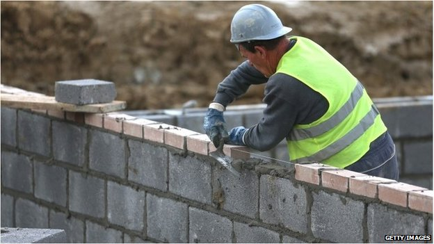 A builder adding bricks to the wall of a house which is being built