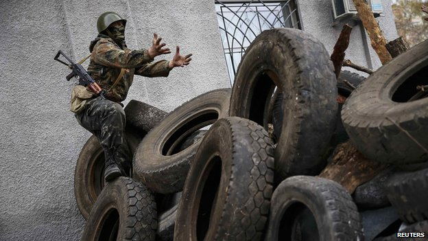 An armed man gestures from a barricade in front of the police headquarters in Slaviansk April 12