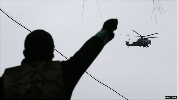 A man gestures while pro-Russian protesters gather at the police headquarters, while a military helicopter flies above, in Sloviansk April 13