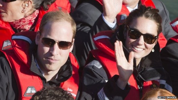 The duke and duchess smile and wave from the jet boat