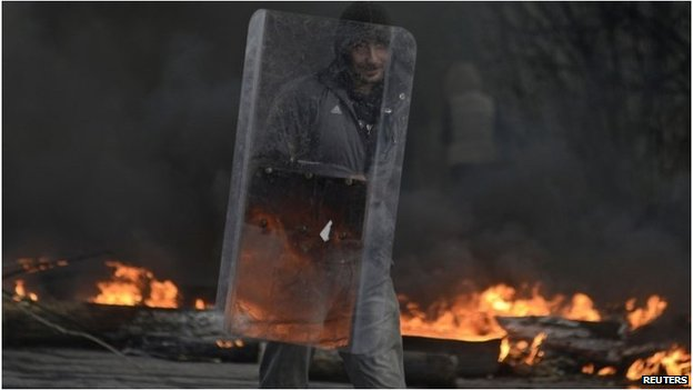 A pro-Russian protester holds a shield at a check point, with black smoke from burning tyres rising above, in Sloviansk April 13