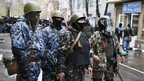 Pro-Russian armed men stand guard while pro-Russian protesters gather near the police headquarters