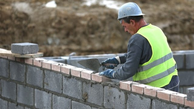 Construction worker lays bricks
