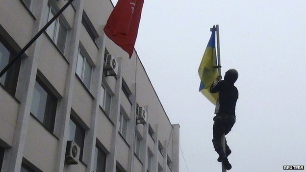 A man climbs up a flagpole to remove a Ukrainian flag in the port city of Mariupol 13/04/2014