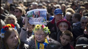 "A woman, wearing a traditional Ukrainian wreath of flowers on her head, holds up a sign with President Vladimir Putin's picture and the words ""Stop lying,"" in Russian"