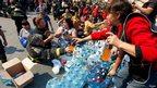 Volunteers deliver bottles of water in Valparaiso, April 13, 2014.