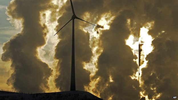 In this Dec. 6, 2010 file photo a wind turbine is pictured in the in front of a steaming coal power plant in Gelsenkirchen, Germany