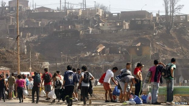 Residents walk carrying their belongings in Valparaiso, April 13, 2014.
