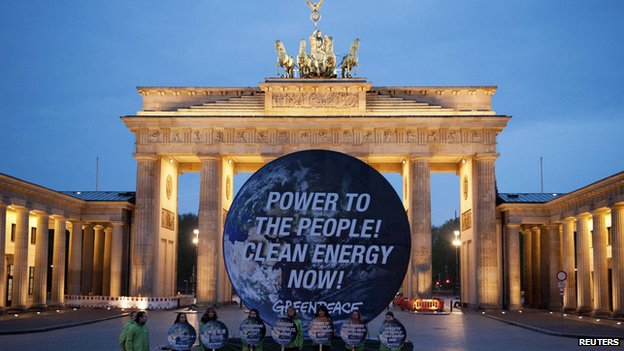 "Members of environmental activist group Greenpeace pose with a giant placard which reads ""Power to the people! Clean energy now"" in front of the Brandenburg Gate in Berlin April 13"