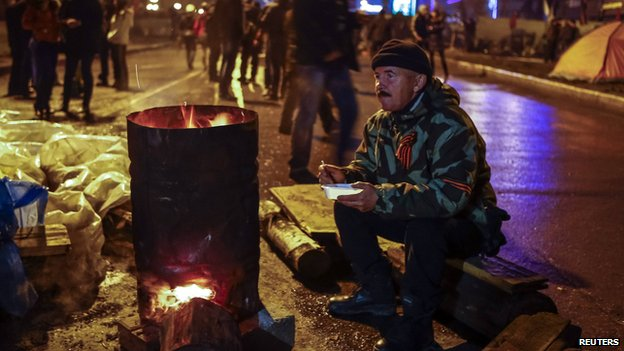 A pro-Russian supporter eats next to a stove on a street near in the seized office of the SBU state security service, in Luhansk, in eastern Ukraine April 13