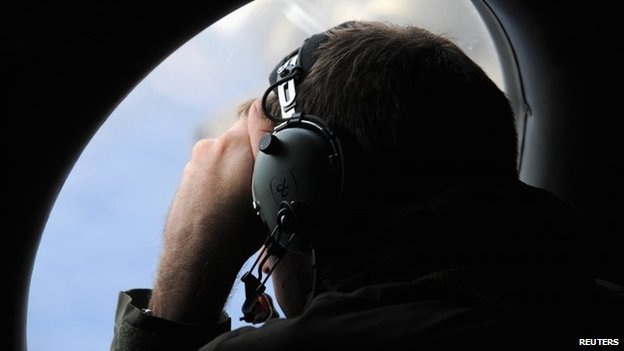 A crew member aboard a Royal New Zealand Air Force (RNZAF) P-3K2 Orion aircraft looks out an observation window as they fly over the southern Indian Ocean to continue the search for missing Malaysian Airlines flight MH370 on 13 April 2014