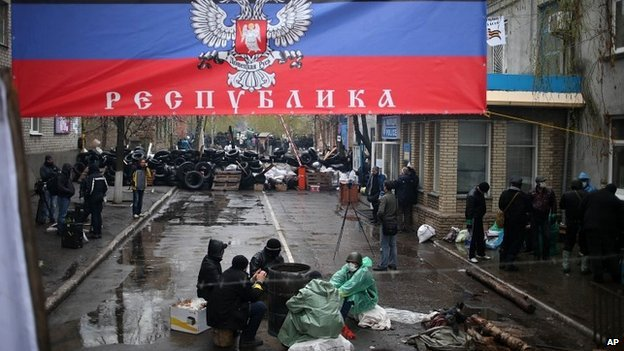 "Pro-Russians outside the seized police station in Sloviansk, with a banner reading ""Donetsk Republic"" - 13 April 2014"
