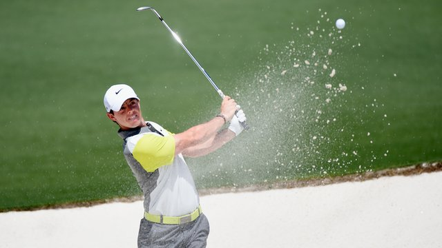 McIlroy plays a bunker shot at the second hole