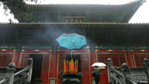 A woman enters a shrine at the Shaolin Temple in Henan Province, China