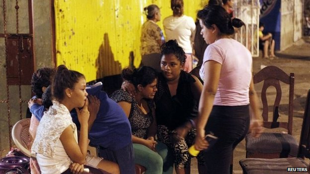 People gather in the streets outside their homes after an earthquake shook Managua on 13 April 2014