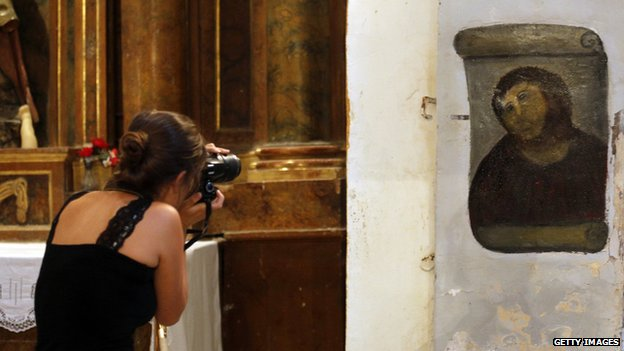 A woman photographs the restored Ecce Homo painting in Zaragoza, Spain