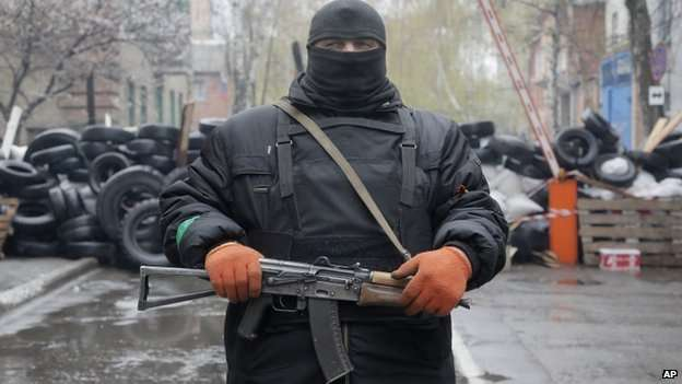 A pro-Russian gunman stands guard at a seized police station in the eastern Ukraine town of Slovyansk on Sunday, April 13, 2014
