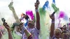 Runners throw coloured powder in the air during the Color Run race in Paris, on 13 April 2014