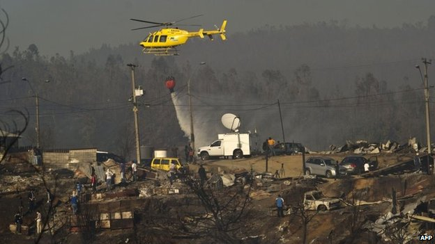 A helicopter empties a bucket of water to fight a fire in Valparaiso, on 14 April 2014