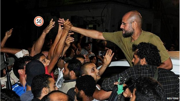 Saif Al-Islam Gaddafi greets supporters in Tripoli on 23 August 2011
