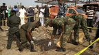 Bomb experts gather evidence at the scene of a bomb blast at Nyanyan in Abuja on 14 April 2014