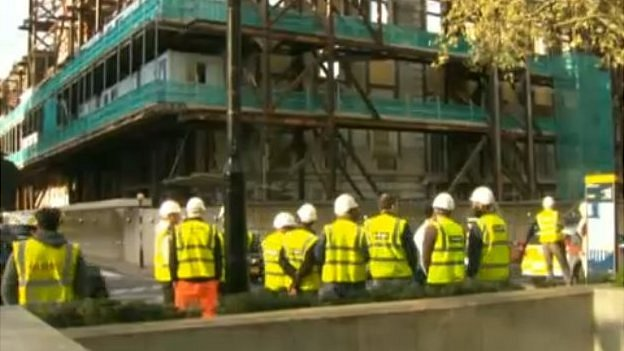 Construction workers gather outside site where workman died