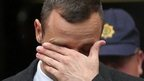 Oscar Pistorius wipes his eyes as he leaves court on 14 April 2014