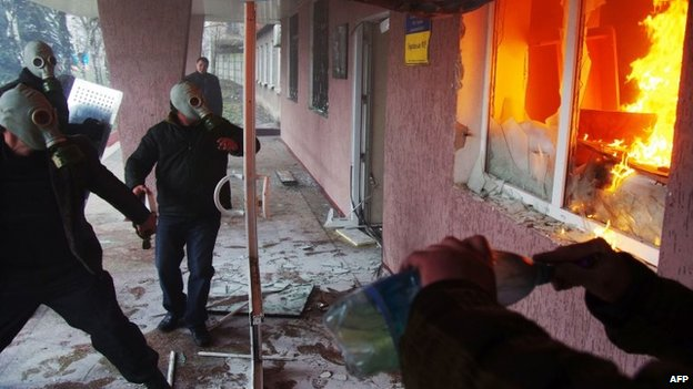 Pro-Russia protester wearing gas masks storm a regional police building as one prepares a petrol bomb in the eastern Ukrainian city of Horlivka