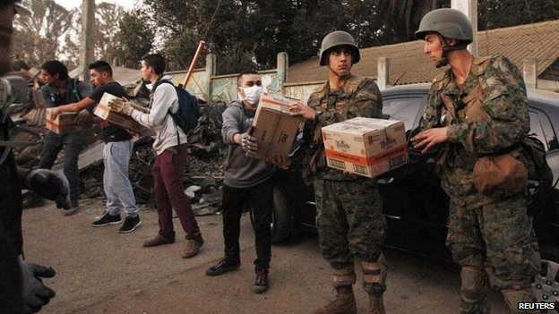 Soldiers (R) deliver food supplies to affected residents in Valparaiso, April 14, 2014.