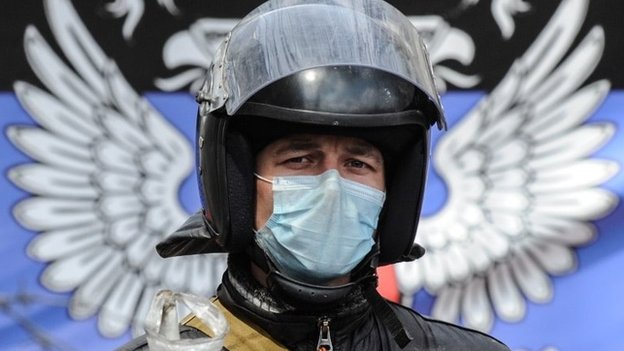 An armed pro-Russian activist stands in front of seized the Ukrainian regional administration building in the eastern Ukrainian town of Sloviansk, Ukraine, on Monday 14 April 2014, with the Russian national sign in the background