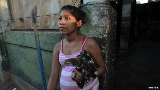A woman carries a chicken as she leaves her home in Managua on 14 April 2014