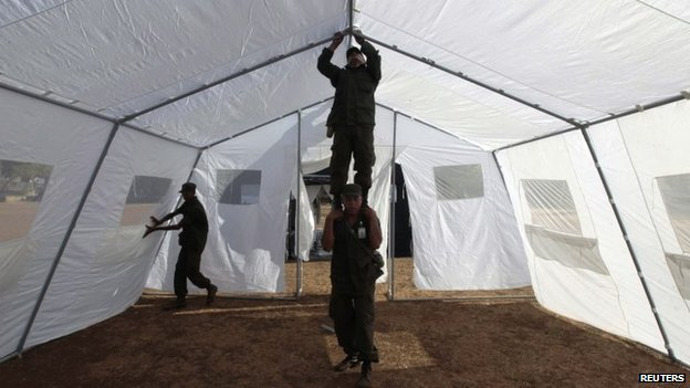 Soldiers prepare a tent to be used as an emergency hospital for earthquake victims in Managua on 14 April 2014