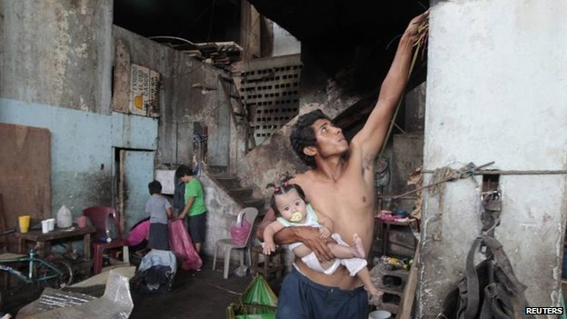 A man living in a building damaged by a previous earthquake in 1972 prepares to evacuate the building after Daniel Ortega's government declared it unsafe on 14 April 2014
