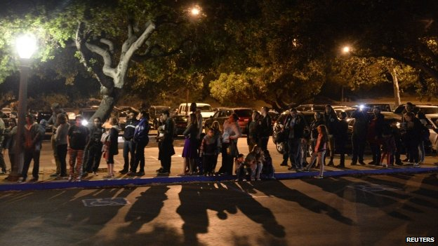 People wait in line to board shuttle buses that will transport them to the Griffith Park Observatory to witness the lunar eclipse from Los Angeles, California, late 14 April 2014