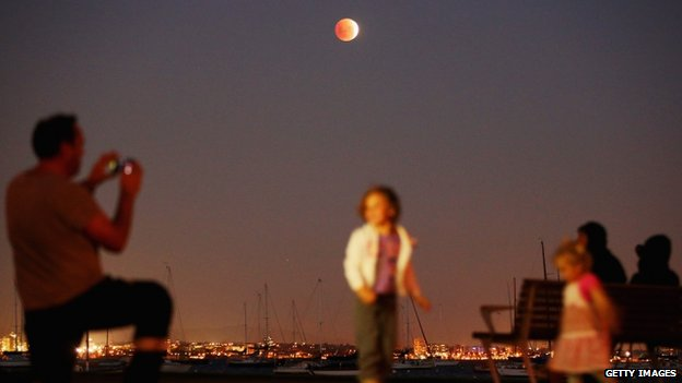 "A man takes a photo of his children as the ""Blood Moon"" rises over the water in Wlliamstown in Melbourne, Australia, 15 April 2014"