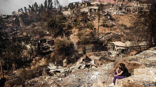 A resident whose home was destroyed by a major fire sits amid the destruction in Valparaiso on 13 April 2014