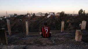 A resident, who lost his home, sits on the edge of a hill where a fire burned several neighbourhoods in Valparaiso city on 14 April, 2014.
