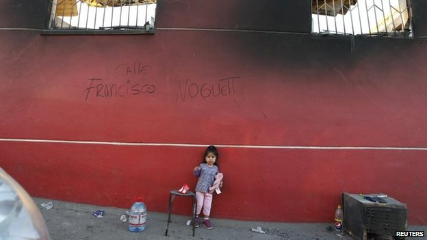 A girl stands in front of a wall of a burned house during the fire that affected several neighbourhoods on the hills in Valparaiso on 14 April 2014