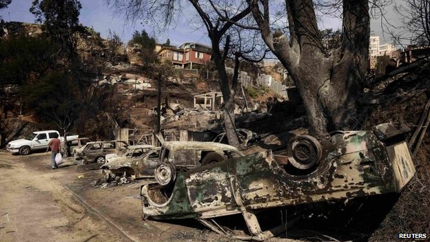 A resident walks past cars destroyed by a major fire in Valparaiso (13 April 2014)