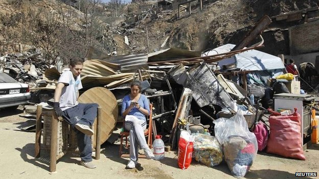Residents sit with belongings in front of remains of houses after a fire burned several neighbourhoods in the hills in Valparaiso on 14 April 2014