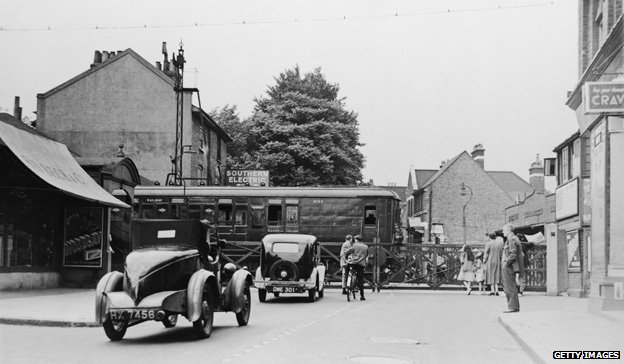 A Southern Electric train passes a level crossing in Mortlake, south-west London, 1937